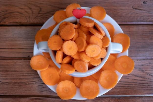 ダイエット、健康、野菜の概念。木製のテーブルの上の白いボウルに生のニンジンの丸いスライス