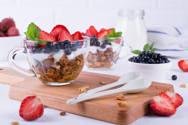 Diet  healthy dessert with yogurt, granola and fresh berries. on white table background