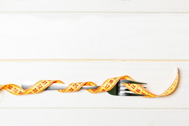 Diet and healthy eating concept with fork wrapped in measuring tape on wooden background. top view of weightloss.