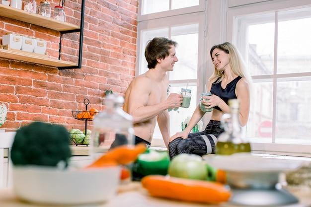 ダイエット、健康的な食事、フィットネスライフスタイル、適切な栄養。キッチンで新鮮なスムージーを飲んで健康志向のカップル。