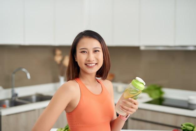 다이어트. 신선한 생 녹색 해독 야채 주스를 마시는 건강 한 먹는 여자.