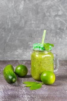 녹색 야채와 과일로 둘러싸인 회색 콘크리트 배경에 빨대와 유리 찻잔 항아리에 시금치와 건강 한 신선한 과일 스무디 음료를 다이어트.