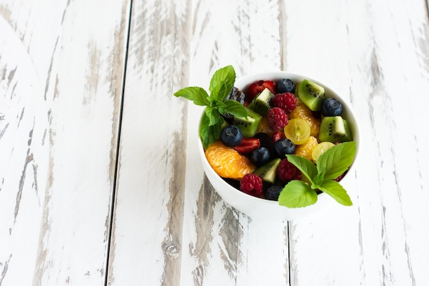 Диета, здоровый фруктовый салат в белой миске с листьями мяты. белый деревянный фон.