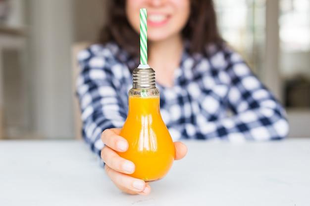 ダイエット、健康的なライフスタイル、デトックスのコンセプト-ボトルに入ったオレンジジュースの女性のクローズアップはランプのように見えます。