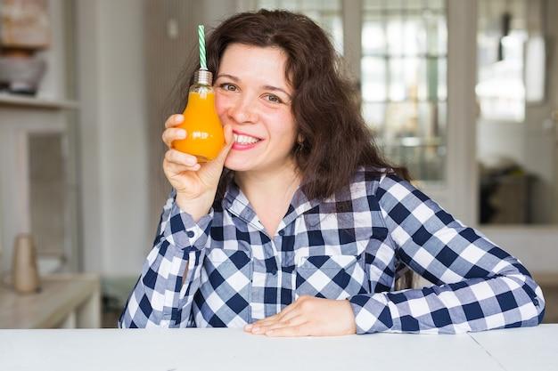 다이어트, 건강한 라이프 스타일, 해독 및 사람들 개념-병에 오렌지 주스를 가진 젊은 여자가 보인다