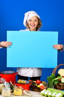 Диета здорового образа жизни женщина-шеф-повар держит доску здоровое меню кухонный гарнитур улыбающийся шеф-повар