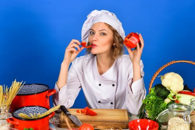 ダイエット健康的なライフスタイルの女性シェフがコショウの健康的なメニューを味わう