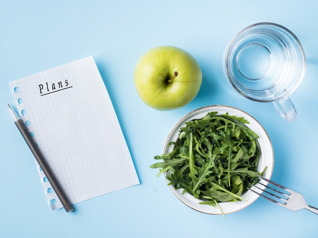 Diet leaves salad green apple a glass of water on blue background.