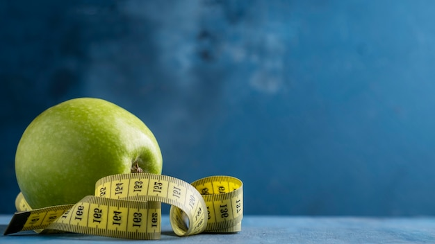 Diet life loss weight concept. green apple and measure tap    over blue surface