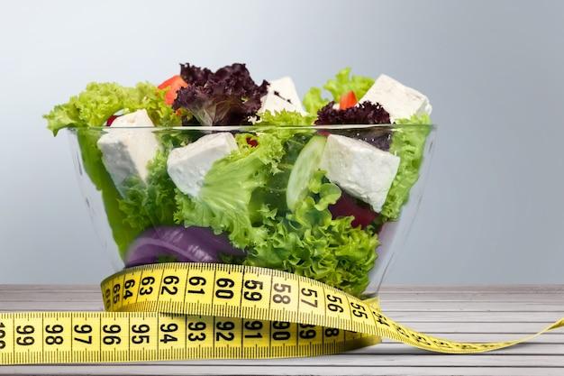 Диетическое питание. салат из овощей в миске с рулеткой