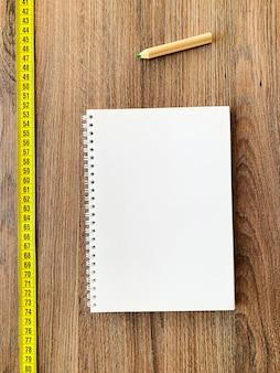 다이어트. 건강 피트니스 배경 책 일기 메모장 및 펜 나무 배경에 테이프를 측정
