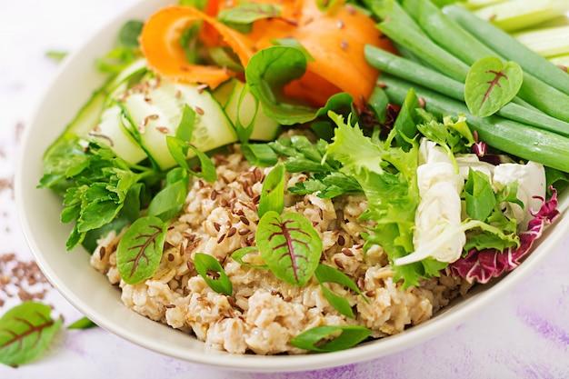 Диетическое меню. здоровый образ жизни. овсяная каша и свежие овощи - сельдерей, шпинат, огурец, морковь и лук на тарелке.