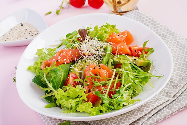 Diet menu. healthy salad of fresh vegetables - tomatoes, avocado, arugula, seeds and salmon