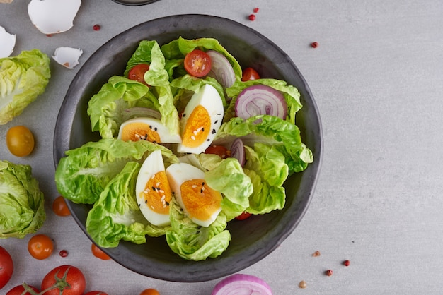 Menu dietetico. sana insalata di verdure fresche pomodori, uova, cipolla. concetto di pasto sano.