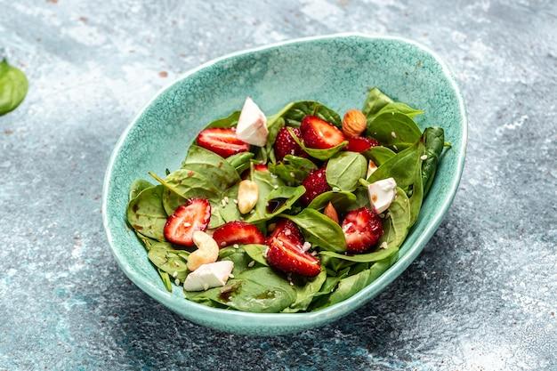 Диетическое меню. полезный салат из свежей клубники, листьев шпината, орехов и сыра фета, бальзамического уксуса. веганская еда. вид сверху.