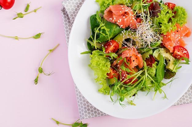 ダイエットメニュー。新鮮な野菜のヘルシーサラダ-トマト、アボカド、ルッコラ、種子、ボウルにサーモン。ビーガンフード。フラット横たわっていた。上面図