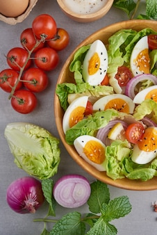 ダイエットメニュー。新鮮野菜のトマト、卵、玉ねぎのヘルシーサラダ。健康的な食事のコンセプト。