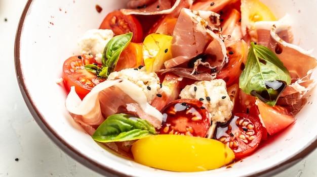Диетическое меню. здоровый салат из свежих овощей с помидорами, шариками из сливочного сыра, хамоном прошутто и листьями базилика на миске. плоская планировка. баннер. вид сверху.