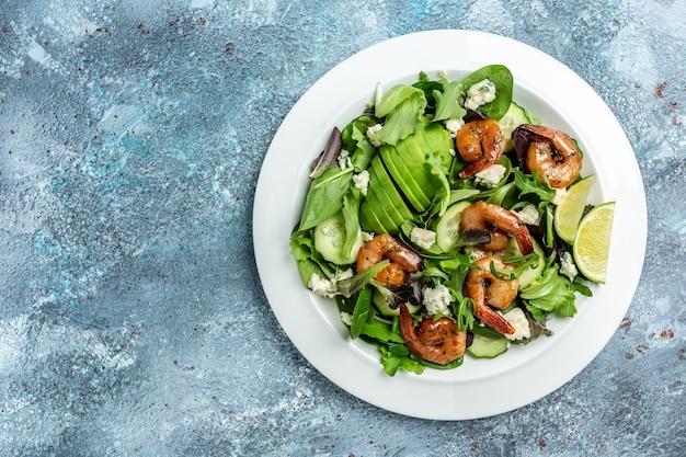 Диетическое меню. полезный салат с авокадо, голубым сыром и копчеными креветками. веганская еда. плоская планировка. вид сверху.