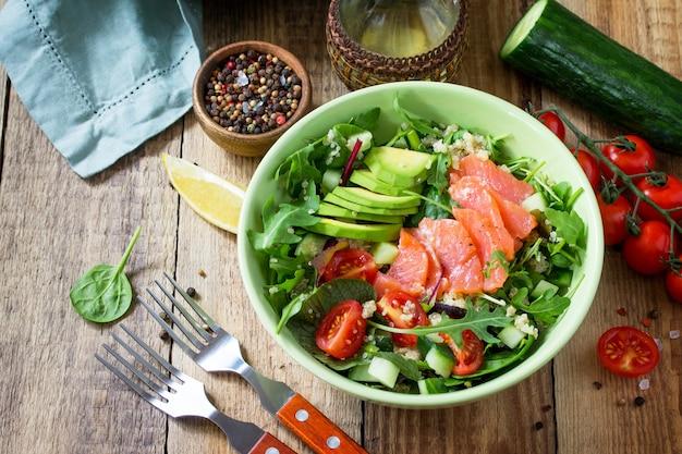 ダイエットメニュー素朴なテーブルにキノアルッコラトマトサーモンとアボカドを添えたヘルシーサラダ