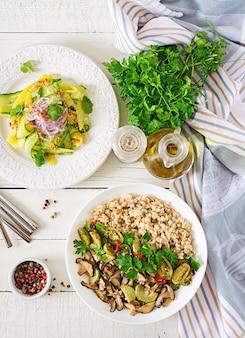 ダイエットメニュー。健康的なベジタリアンの食事-ボウルにキノコのシイタケ、ズッキーニ、オートミールのおridge。ビーガンフード平干し。上面図