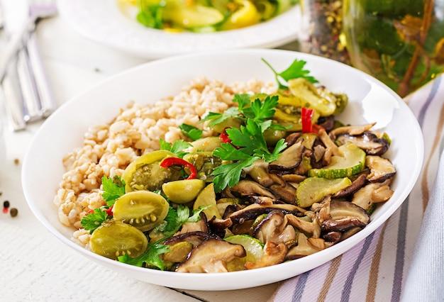 ダイエットメニュー。健康的なベジタリアンの食事-ボウルにキノコのシイタケ、ズッキーニ、オートミールのおridge。ビーガンフード