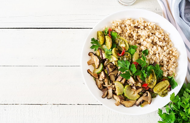 Diet menu. healthy vegetarian meal - mushrooms shiitake, zucchini  and oatmeal porridge on bowl. vegan food. flat lay. top view