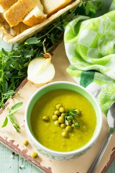 Диетическое меню суп-пюре с зеленым горошком в миске на кухонном деревянном столе