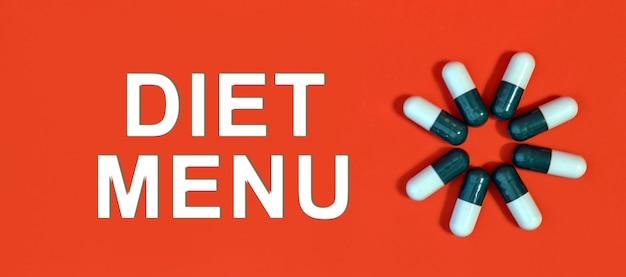ダイエットメニュー-ピルカプセルと赤い背景の上の白いテキスト
