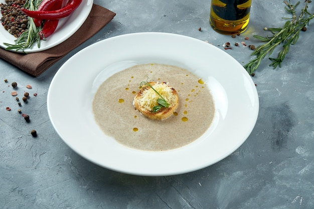Диетический грибной крем-суп с гренками с сыром в белой тарелке