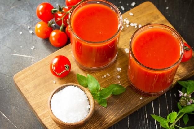 ダイエット栄養の概念暗い石のテーブルにトマトジュースとフレッシュトマトのグラス