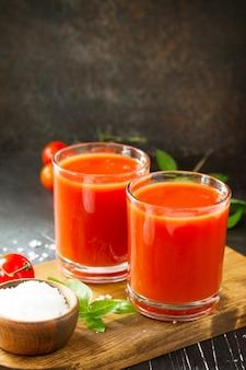 ダイエット栄養の概念石のテーブルにトマトジュースとフレッシュトマトのグラス