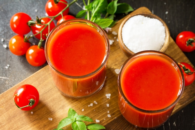 Diet nutrition concept glasses with tomato juice closeup and fresh tomatoes on a dark stone table