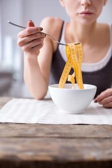 Одержимость диетой. депрессивная женщина с недостаточным весом думает о своем весе, будучи одержимой диетой