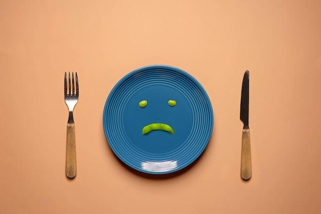 ヘルスケアの概念における食事療法または食欲不振。摂食障害。体重を減らすようにしてください。フォークとナイフに囲まれたプレート上の緑大豆。不幸な食べ物。上面図