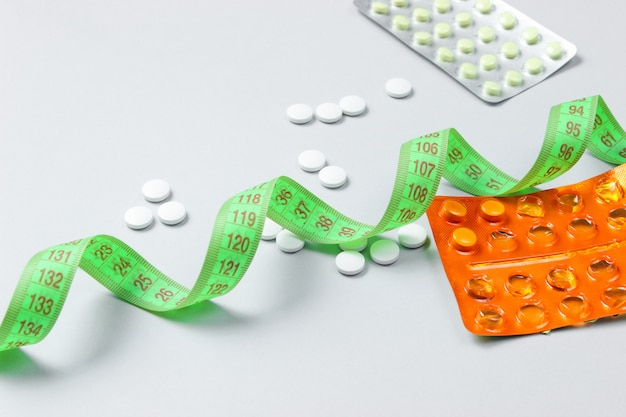 Diet pills and measuring tape on a gray surface