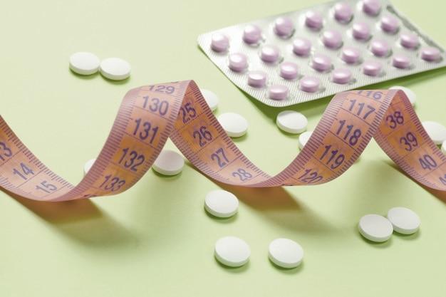 Диетические таблетки. правитель и таблетки на зеленом фоне. концепция потери веса