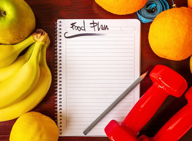 Diet plan. diet plan and a fruits and dumbbells lying on a wooden surface