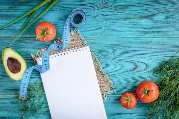食事療法は空のノート、メニューまたは栄養プログラムを計画します。青い木製の背景に新鮮な野菜。