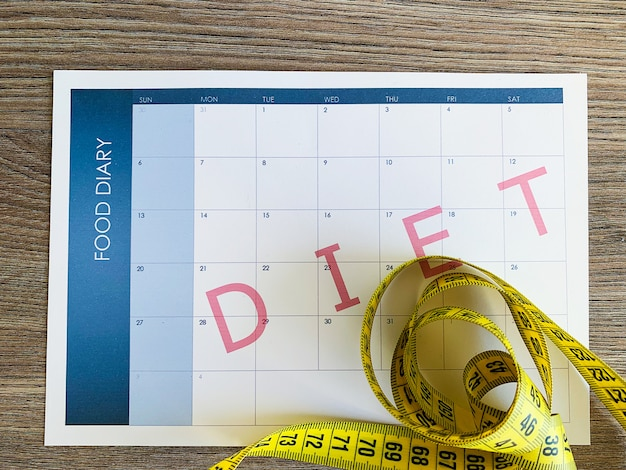 Diet plan. measuring tape and diet plan on wooden background.