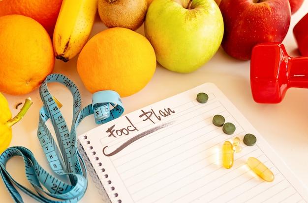 План диеты, меню или программа, потеря веса, измерительная лента, гантели и диетическое питание, свежие фрукты на белом столе