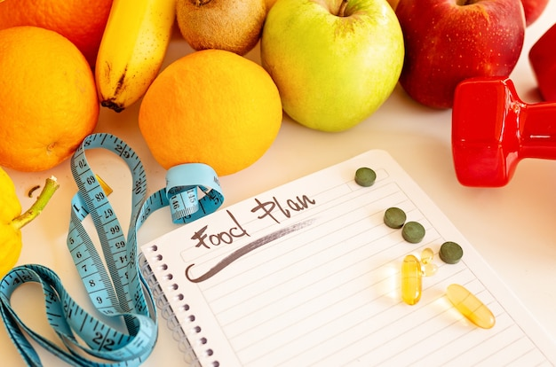 Diet plan, menu or program, weight loss, measuring tape, dumbbells and dietary food fresh fruit on a white table