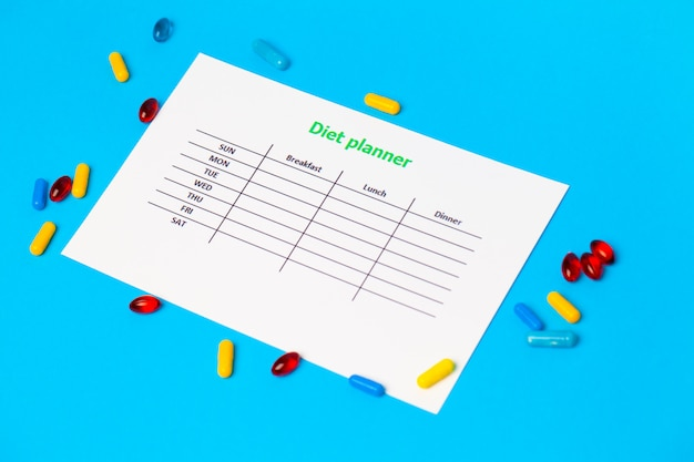 Diet plan and weight loss pills on blue.