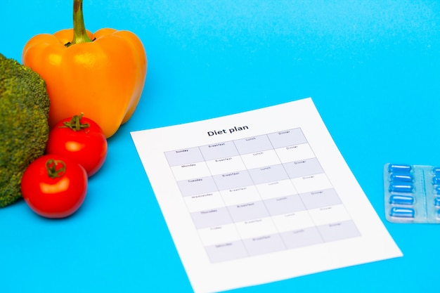 Diet plan, for weight loss pills and fresh vegetables on blue.