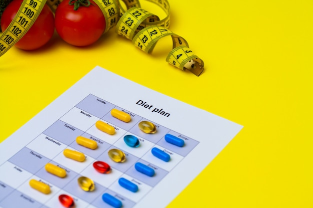 Diet plan for weight loss pills and fresh vegetables on yellow.