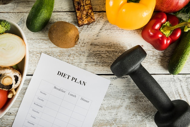 Diet plan with vegetables and dumbbells on wooden backdrop