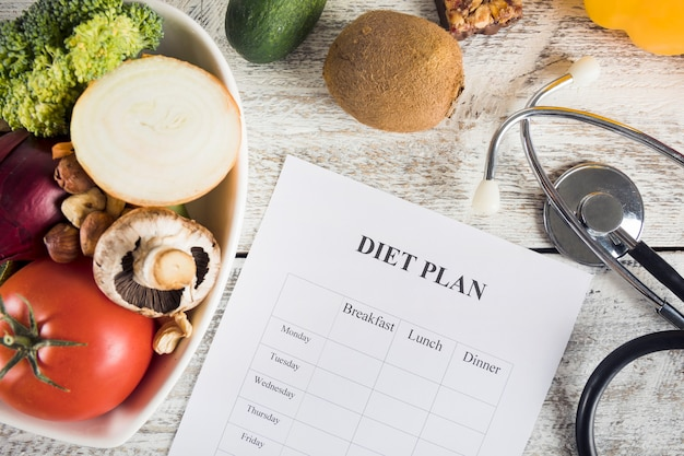 Diet plan with vegetables and stethoscope on wooden desk