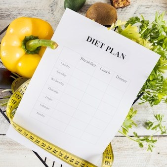 Diet plan wrapped with measuring tape over fresh vegetables