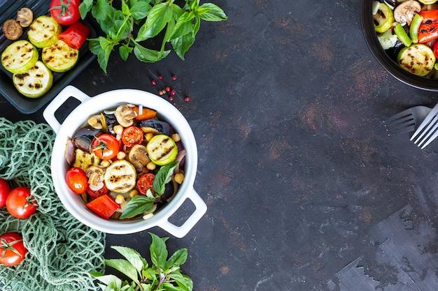 食事療法、適切な栄養、野菜のグリル、暗い背景の食材。フレーム。ベジタリアンフード。上面図。コピースペース