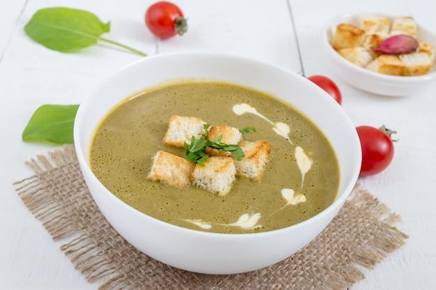 Диетический суп-пюре со шпинатом и гренками в белой миске. правильное питание.